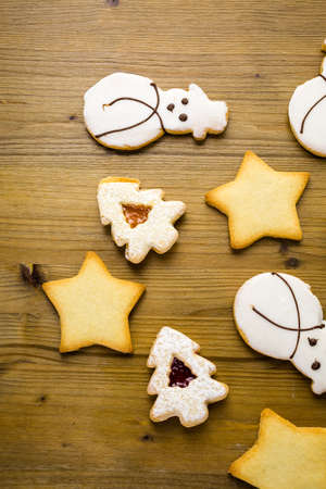Sugar cookies in shape of snowman, stars, and christmas tree on wood table.