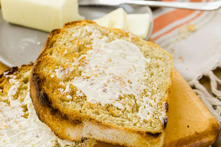 Toasted slices of freshly baked sourdough bread with butter. Imagens