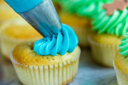 patty cake: Making multicolor cupcakes for kids birthday party.