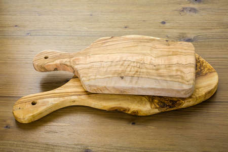 Olive wood cutting board on wood table. Imagens
