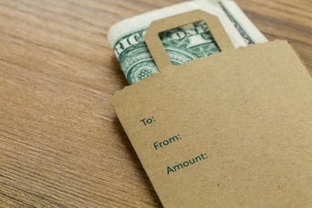 gratuity: Tips for services in a small envelope on the table. Stock Photo
