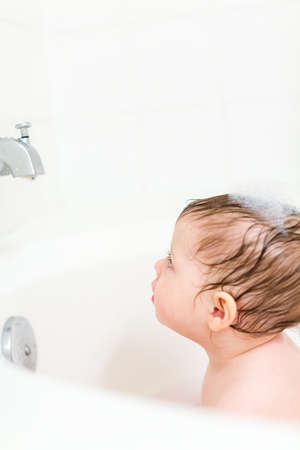 Cute baby girl taking a bath with bubbles. photo