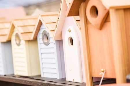 Row of birdhouses made from wood on the display.