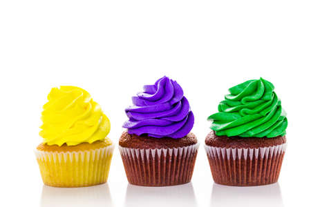 fat tuesday: Cupcakes decorated with bright color icing for Mardi Gras party.