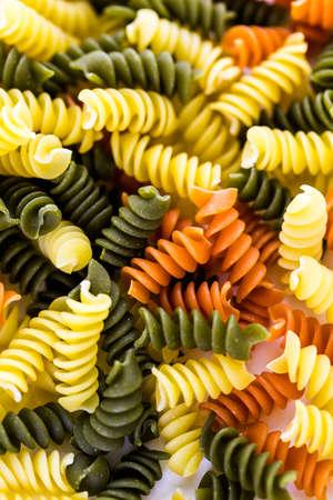 rotini: Organic dry pasta on a white background.