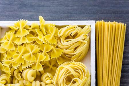 rotini: Variety og organic dry pasta on wood board.