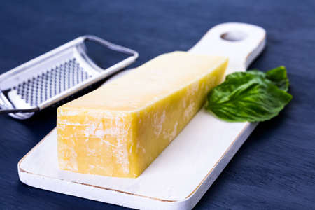 grader: Slice of parmesan cheese on the board.