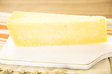 Parmesan: Slice of parmesan cheese on the board.