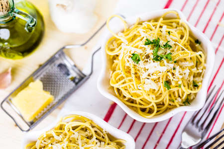 garnish: Cheese and pepper spaghetty with green garnish in white bowls. Stock Photo