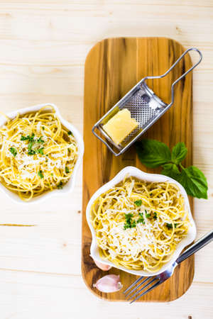 grader: Cheese and pepper spaghetty with green garnish in white bowls. Stock Photo