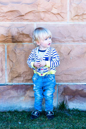 boy 12 year old: Cute toddler boy posing for camera in the city.