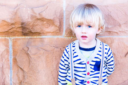 13 year old boy: Cute toddler boy posing for camera in the city.