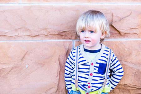 12 13: Cute toddler boy posing for camera in the city.