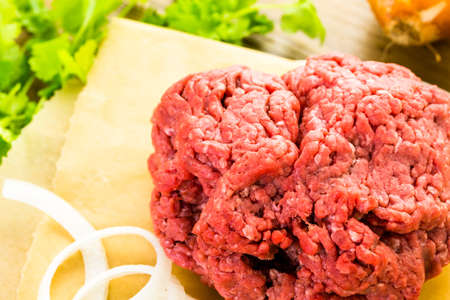 vegetus: Ground beef on the table with other ingredients for recipe.