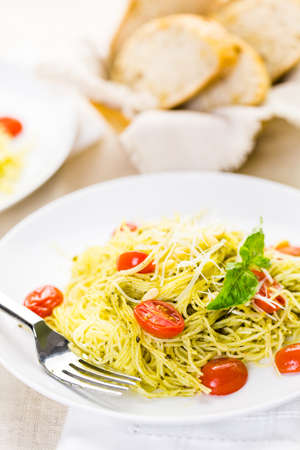angel hair: Homemade angel hair pasta with pesto sauce and roasted cherry tomatoes. Stock Photo