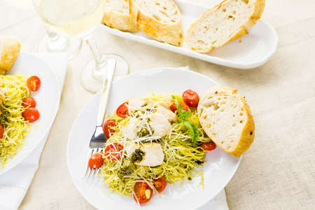 Homemade angel hair pasta with pesto sauce, roasted cherry tomatoes and grilled chicken.