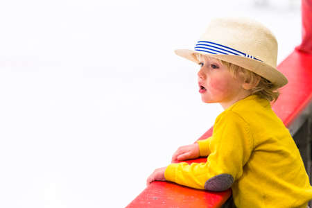 12 13: Toddler boy watching local hockey game.