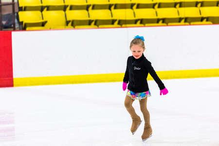 figure skater: Young figure skater practicing at indoor skating rink.