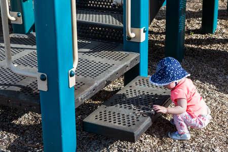tot: Toddler girl playing on tot lot on Spring day.