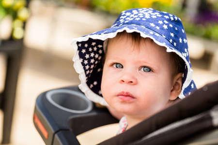 garden center: Cute toddler girl in strollet at garden center. Stock Photo