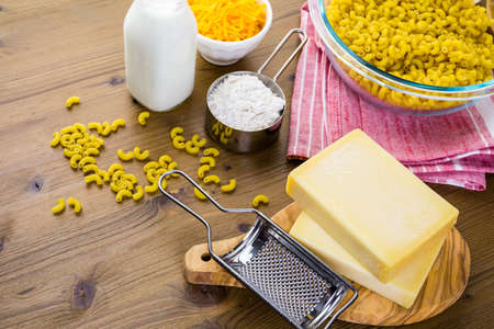 Ingredients for preparing macaroni and cheese on a wood table.