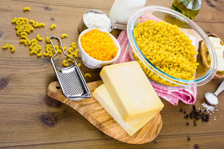 cuisines: Ingredients for preparing macaroni and cheese on a wood table.