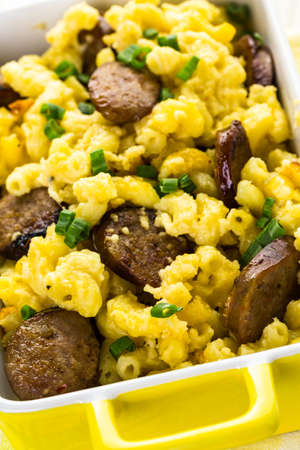 italian sausage: Baked macaroni and cheese with Italian sausage and garnished with chives.