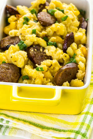 vegetus: Baked macaroni and cheese with Italian sausage and garnished with chives.