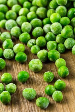 vegetare: Organic frozen baby sweet peas on wood board.