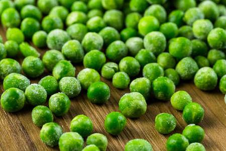 vegetabilis: Organic frozen baby sweet peas on wood board.
