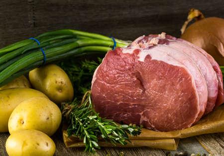 vegetabilis: Organic pork lion roast with rosemary on wood farm table.