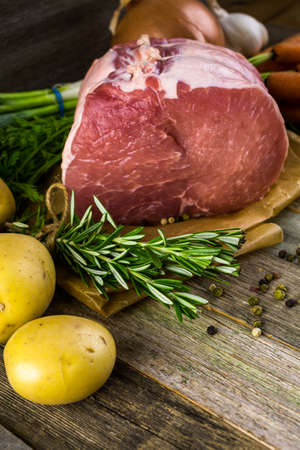 vegetare: Organic pork lion roast with rosemary on wood farm table.