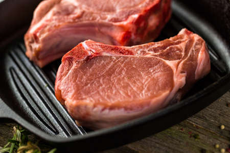vegetus: Organic pork lion chops of thick cut on cast iron frying pan.