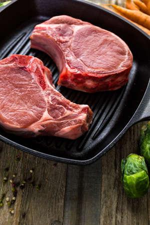 etymology: Organic pork lion chops of thick cut on cast iron frying pan.