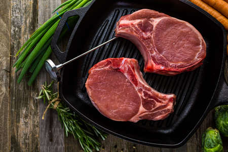etymology: Organic pork lion chops of thick cut on cast iron frying pan.