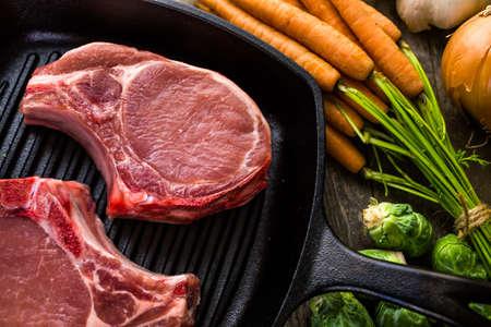 vegetabilis: Organic pork lion chops of thick cut on cast iron frying pan.