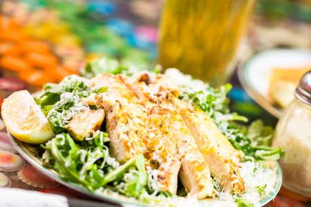 Arugula salad with grilled chicken in Italian restaurant.