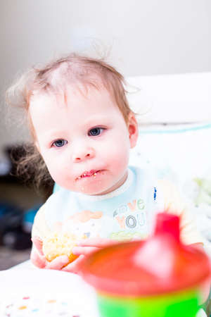 messy room: Cute toddler girl wating lunch in her high chair.