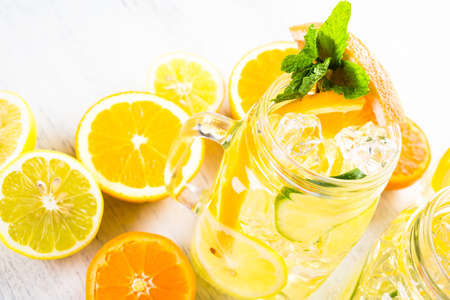 Infused water with fresh citrus fruits and ice. Imagens