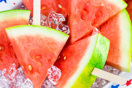 popsicles: Watermelon slice popsicles on serving plate with ice.