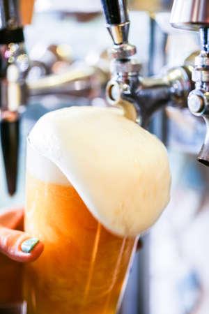 barra: Bartender verter la cerveza de barril en el bar. Foto de archivo
