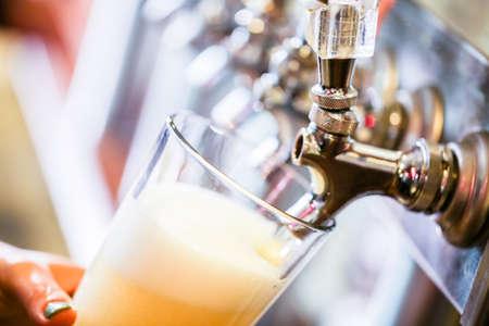 beer: Bartender verter la cerveza de barril en el bar. Foto de archivo