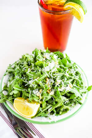 vegetus: Arugula salad with pine nuts on the plate in Italian restaurant.