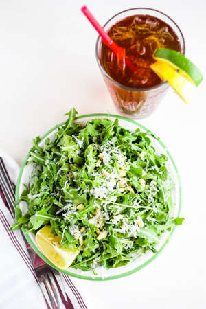 vegetabilis: Arugula salad with pine nuts on the plate in Italian restaurant.
