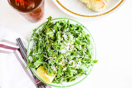 vegetare: Arugula salad with pine nuts on the plate in Italian restaurant.