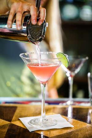 Bartender preparing Cosmopolitan drink for customer.