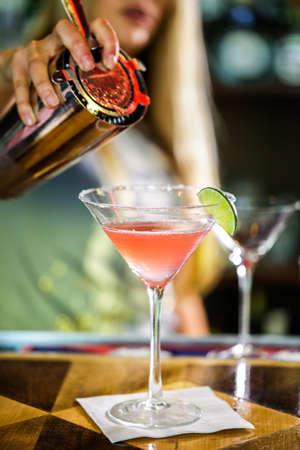 bartender: Bartender preparing Cosmopolitan drink for customer.
