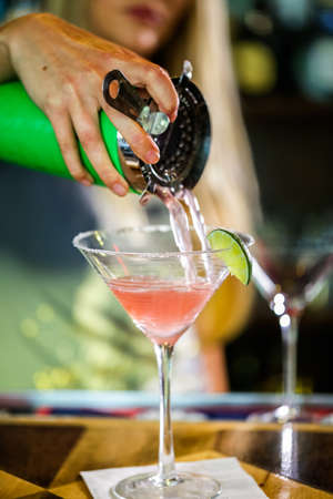 cosmopolitan: Bartender preparing Cosmopolitan drink for customer.