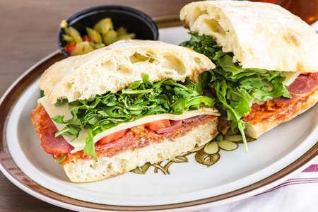 Italian sub sandwich with arugula on ciabatta bread.