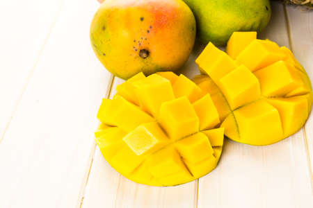 Fresh organic mango and pineapple on a white wood board. Imagens